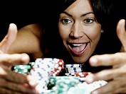 Woman pulling gambling chips towards herself, smiling, close-up