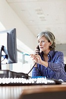 Woman using telephone at desk in office, pointing at monitor with pen