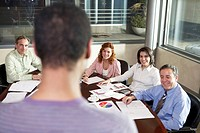Rear view of businessman leading meeting, focus on colleagues at table