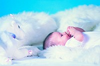 Baby lying on white fluffy blanket