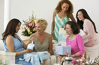 Group of women at baby shower, pregnant woman admiring gift