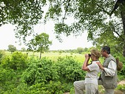 Mature couple in African bush, woman using binoculars, side view