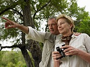 Mature couple in African bush, woman holding binoculars, man pointing