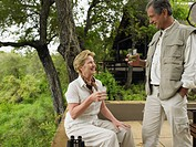 Mature couple having drinks on terrace at lodge, smiling