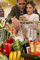 Father and daughter (8-10) in supermarket using mobile phones