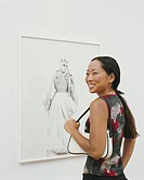 Woman in art gallery, turning to one side, smiling