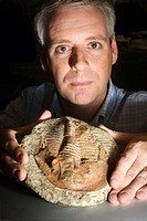 Dr Andrew Parker (b. 1967), Australian biologist, holding a trilobite fossil. Parker is a research fellow at Oxford University. He was the first to di...