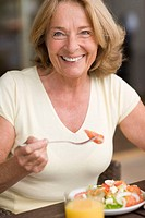 Healthy eating. Middle-aged woman eating a salad. Salad leaves, fruits and vegetables are low in fat and salt and rich in vitamins and minerals, makin...