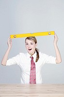 Businesswoman balancing a spirit level on her head.