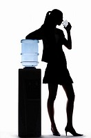 Silhouette of businesswoman drinking water