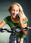 Girl talking on the mobile phone while cycling