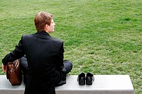 Businessman sitting on the bench with his shoes by the side (thumbnail)
