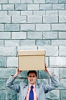 Businessman carrying a box on his head.