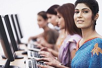Close-up of four businesswomen sitting in front of computers