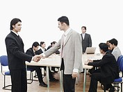 Side profile of two businessmen shaking hands in a meeting