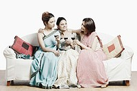 Close-up of three young women sitting on a couch holding wineglasses