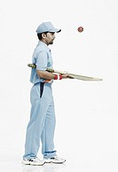 Side profile of a young man playing with a cricket bat and a cricket ball