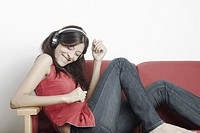 Young woman sitting on a couch wearing headphones and listening to music