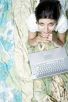 High angle view of a young woman in front of a laptop