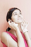 Close-up of a young woman wearing earphones listening to music