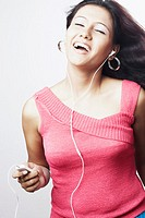 Close-up of a young woman with her eyes closed listening to an MP3 player