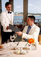 Waiter giving menu to customer in restaurant