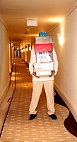 Hotel bellboy carrying gifts in the corridor