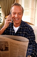Mature man reading newspaper and talking on cell phone