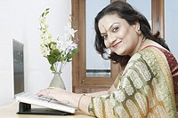 Side profile of a mature woman sitting in front of a laptop