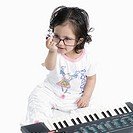High angle view of a baby girl sitting in front of an electric piano