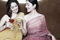 Two young women sitting on a couch toasting with martini glasses