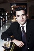 Portrait of a businessman sitting at a bar counter with a glass of whiskey