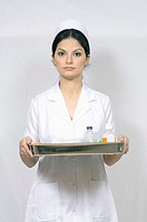 Portrait of a female nurse holding a tray