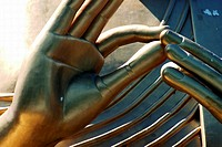 Close-up on the fingers of a golden statue