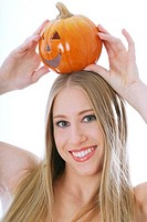 Woman placing a carved pumpkin on her head