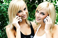 Twin sisters talking on their mobile phones