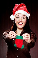 Woman in christmas hat holding a christmas sock (thumbnail)