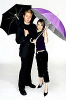 Couple holding umbrellas