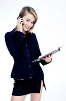 Businesswoman holding a document while talking on the mobile phone