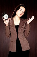 Businesswoman with puzzled look holding an alarm clock