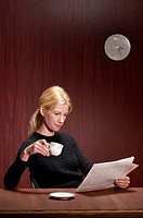 Businesswoman drinking coffee while reading newspaper