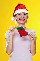 Woman in christmas hat holding a christmas sock