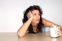 Bored woman holding a glass of milk