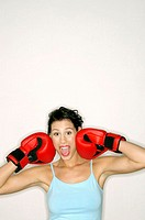 Woman with boxing gloves boxing her own face