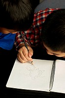 Boy showing off his drawing skill to his younger brother.