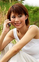 Woman sitting on a grass field talking on the handphone.