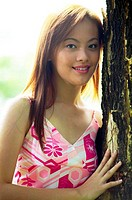 Woman in pink dress posing beside a tree.