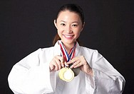 Taekwando practitioner showing off her gold medals.