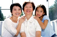 Girl posing with her mother and grandmother.