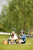 Old couple picnicking with their grandsons in the park.